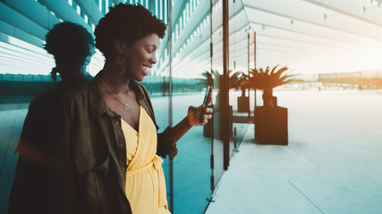Laughing black girl having an online video call with her friend via smartphone near the glass wall; cheerful young African female entrepreneur answering message on her cellphone near office entrance