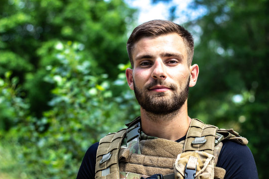 Portrait of a soldier in body armor and body kits. Young guy with a beautiful beard and haircut.
