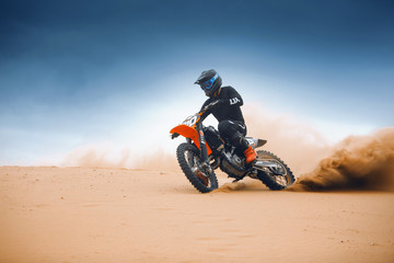 Motorcyclist on a cross-country motorcycle go fast at the desert Fototapete