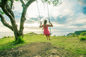 woman swinging on a swing on a tropical island