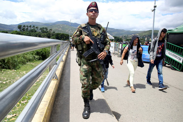 A member of the Colombian security forces guards as people cross the Colombian-Venezuelan border over the partially opened Simon Bolivar international bridge in Cucuta