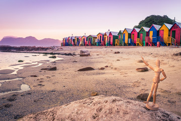 View of the beautiful sunset over False Bay from Kalkbay with little coloured houses on the beach, with little wooden manikin posing, Cape Town, South Africa