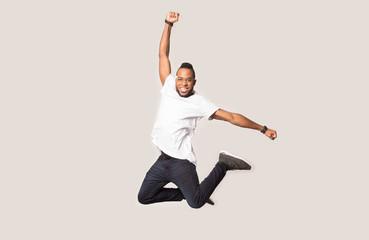 Happy joyful black man jumping high in photo studio.