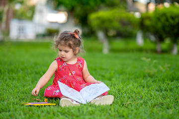 Little  girl learning for coloring or drawing paint on green grass in nature at garden