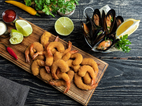 fried breaded shrimps, mussels served with lime on wooden board, delicious deep, red, white sauce