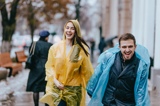 Funny and loving guy and girl in yellow and blue raincoats are running in the rain outside.