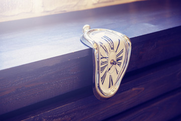 Indoor clocks of unusual shape on a brown wooden background. Time flows
