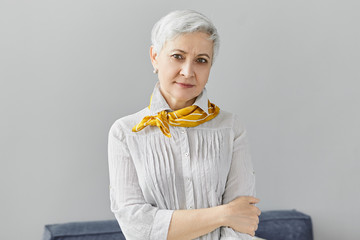 Style, fashion, maturity and elegance concept. Portrait of good looking attractive middle aged Caucasian woman with stylish hairdo and neat make up, about to going out, wearing yellow scarf and blouse