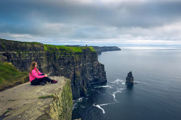 Young woman sitting at the cliffs of Moher