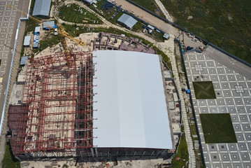 aerial view of a large industrial building with a tower crane