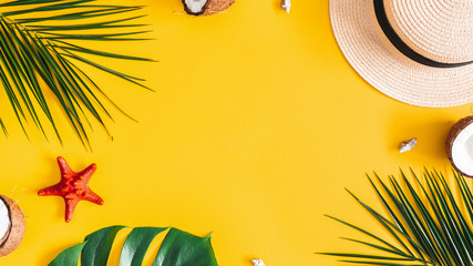Summer composition. Tropical palm leaves, hat, coconut on yellow background. Summer concept. Flat lay, top view, copy space