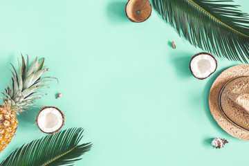 Summer composition. Tropical palm leaves, hat, fruits on mint background. Summer concept. Flat lay, top view, copy space