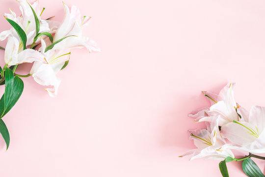 Flowers composition. Lily flowers on pastel pink background. Flat lay, top view, copy space