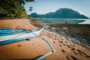 View of El Nido bay with local banca boat in front at low tide, picturesque scenery in the afternoon, Palawan, Philippines