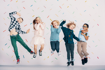 Girls and boys having fun while jumping against colorful wallpaper. Friends in the school