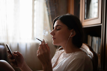 woman sitting at the chair at home, listen to the music and smoking a cigarette .