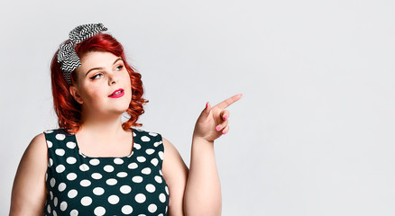 Pin up a female portrait. Beautiful retro fat woman in polka dot dress with red lips and old-style haircut