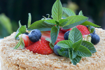 Homemade cake decoration with blueberries, strawberries and peppermint herb