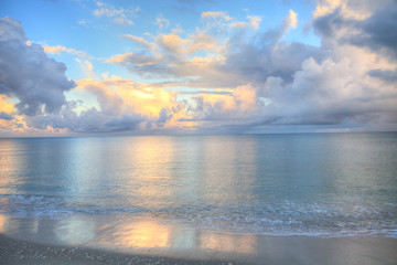 Ocean rolls in under puffy clouds on North Naples Beach at sunrise Fotomurales
