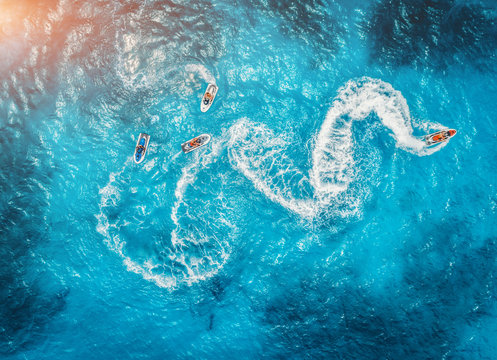 Aerial view of floating water scooter in blue water at sunset in summer. Holiday in Indian ocean, Zanzibar, Africa. Top view of jet ski in motion. Tropical seascape with moving motorboat. Extreme