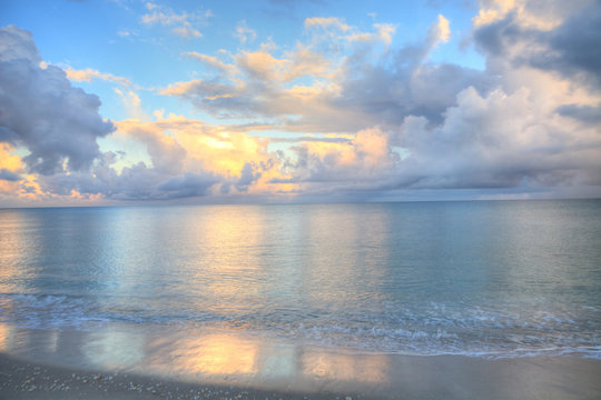 Ocean rolls in under puffy clouds on North Naples Beach at sunrise