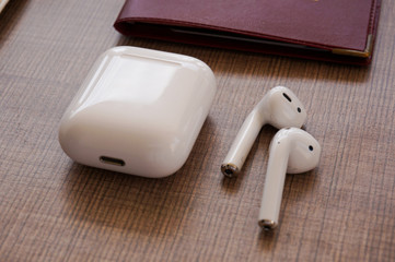 Life style flat lay white air pods close up wooden background