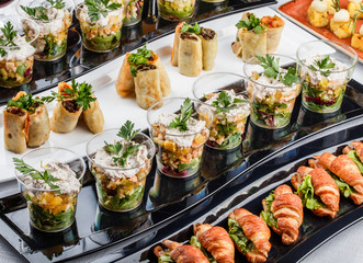 Mini appetizers with salmon fish, caviar, cheese, prawn, shrimp and greens on banquet table. Gourmet food close up, snack, antipasti, Seafood platter