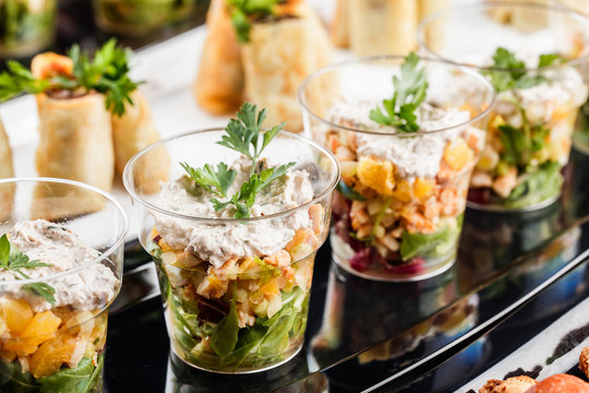 Delicious appetizers with salmon, shrimp, cheese and greens in glass cups on banquet table. Gourmet food close up, snack, antipasti, Seafood platter