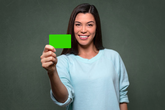 Young beautiful college student holding blank card, possibly credit, membership, I.D., library, identification