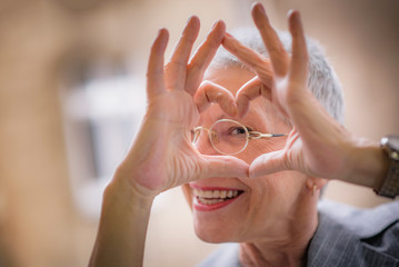 Cute senior old business woman making a heart shape with her hands and fingers