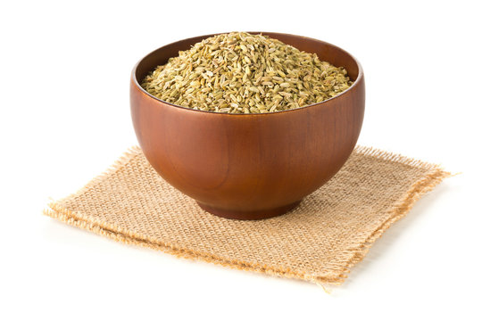 Dried fennel seeds in wooden bowl over white background