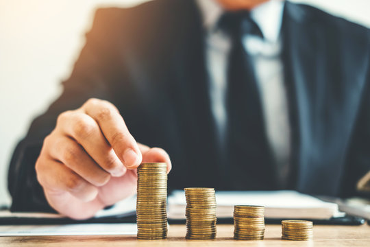 Business man Accounting Calculating Cost Economic budget putting Row and coin Write Finance ,investment and saving concept
