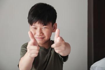 Smiling Asian tween boy pointing finger gun gesture, fun cheeky happy youth portrait