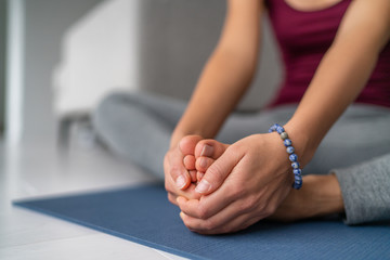 Obraz Yoga leg stretches woman at home. Seated butterfly legs stretch holding soles of feet together. Closeup of hands holding barefoot feet on exercise mat. - fototapety do salonu