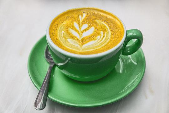 Ayurvedic turmeric latte coffee cup. Golden milk froth with turmeric powder coloring anti-inflammatory food detox.