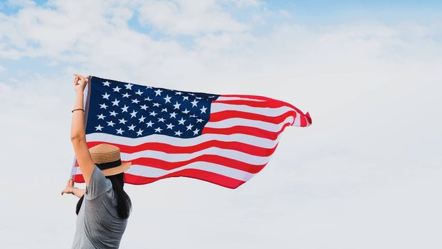 Young woman holding American flag on blue sky background with copy space.Vintage tone.Concept of America celebrate 4th of July.