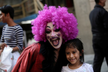 "A participant dressed in drag poses for a picture with a child during the ""Drag Queen Story Hour"" event, which according to organizers involves participants reading stories to children for an hour, in downtown Monterrey"
