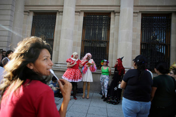 """Participants dressed in drag read a book during the """"Drag Queen Story Hour"""" event, which according to organizers involves participants reading stories to children for an hour, in downtown Monterrey"""