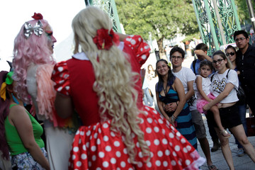 """People listen to participants dressed in drag while they read a book during the """"Drag Queen Story Hour"""" event, which according to organizers involves participants reading stories to children for an hour, in downtown Monterrey"""