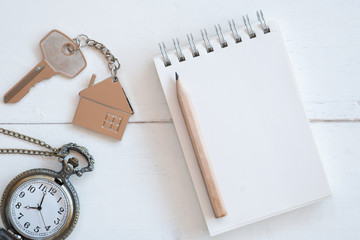 House key with home keyring, blank notebook and pencil on white wood table background