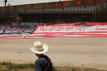 Roberto Marquez, also known as Robenz, looks on after placing a large banner in the likeness of the U.S. flag in protest of the latest migration agreement between Mexico and the United States, near a border wall in El Paso, as pictured from Ciudad Juarez