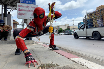 A man dressed in a Spider-Man costume hawks flower garlands at a road junction in Tha Tang