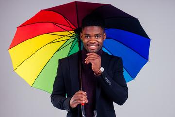 smiling businessman in suit coat wool with multi-coloured umbrella white background studio