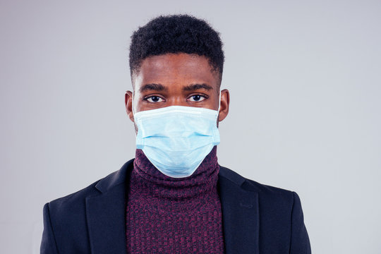 African american male wearing on a gauze mask and warm coat and sweater white background studio. cold season winter autumn or spring.