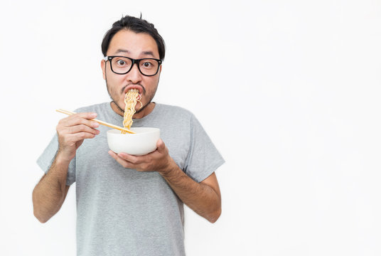 Young handsome trendy asian nerd man eating yummy hot and spicy instant noodle using chopsticks isolated on white background. Asian guy servile end of the month with cheap food.
