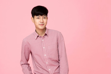 Portrait of young handsome Asian man in pink shirt