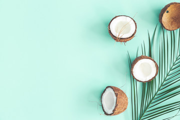 Summer composition. Coconut, palm leaf on mint background. Summer concept. Flat lay, top view, copy space