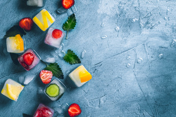 Ice cubes with fruit and broken ice on a stone blue background with mint leaves and fresh fruit. Mint, strawberry, cherry, lemon, orange. Flat lay, top view