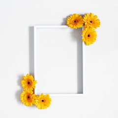 Flowers composition. Yellow gerbera flowers, photo frame on gray background. Flat lay, top view, copy space