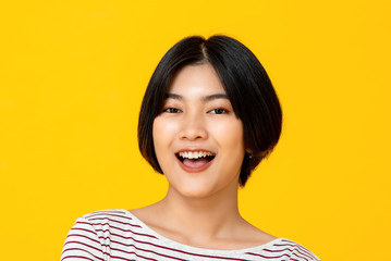 Young beautiful smiling Asian woman in yellow background